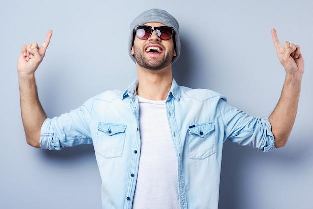 저것 봐! 선글라스와 모자를 쓰고 회색 배경에 서서 웃고 있는 잘생긴 젊은 남자