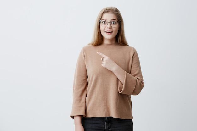 あれ見てよ!ブロンドの髪を持つ驚くびっくりした女性は、スタイリッシュなメガネをかけて、式、灰色の背景上のコピースペースで人差し指でポイントに衝撃を与えた。驚きと興奮のコンセプト