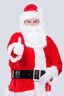 저것 봐! 회색 배경에 서 있는 동안 가리키는 전통적인 산타 클로스