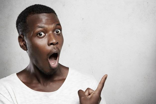 Посмотри на это! молодой привлекательный шокированный темнокожий служащий смотрит в полном недоумении, указывая пальцем на пустую стену с местом для копирования вашего рекламного контента, недоуменно недоумевая