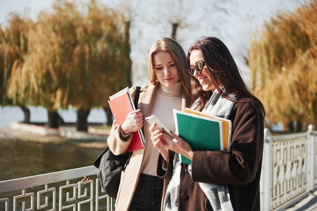 Посмотрите на эти результаты экзамена. две студентки гуляют в парке по мосту, держа в руках блокноты