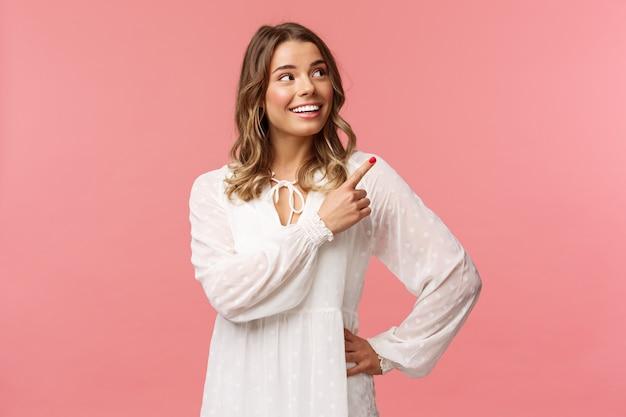 이거 봐요. 밝고 사랑스러운 금발 유럽 여자 20 대 흰색 귀여운 드레스, 빛나는 미소로 오른쪽 위 모서리를 가리키고, 기쁘게보고, 좋은 제안에 만족, 분홍색 벽