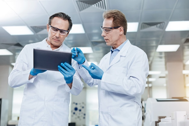 이걸 봐. 유능한 실험실 조교가 반 자세로 서서 동료에게 피가 묻어있는 테스트 튜브를 보여주는 동안 보호 안경을 착용