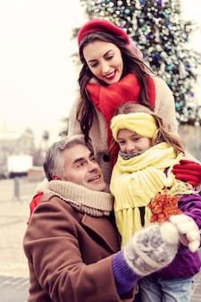 이것 좀봐. 그녀의 가족 근처에 서있는 동안 양성을 표현하는 귀여운 갈색 머리 여자