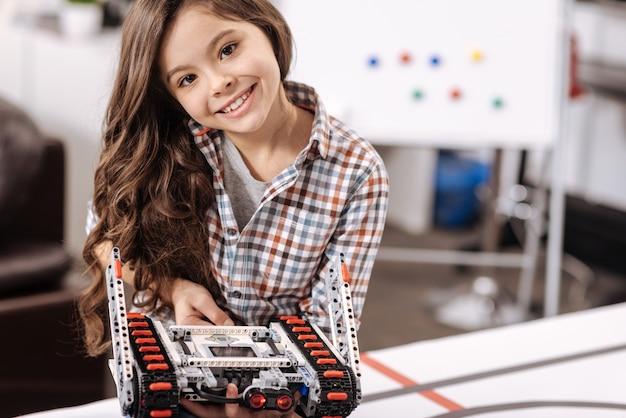 この電子玩具を見てください。ロボット工学研究室に座って、喜びを表現しながらサイバーロボットを保持している魅力的な笑顔の楽しい女の子