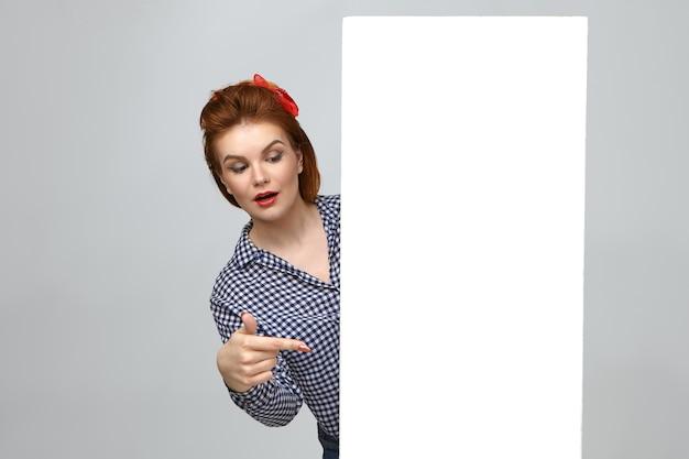 이것 좀봐. 상품을 홍보하는 소녀 핀처럼 옷을 입고 세련된 매력적인 젊은 아름다운 여성의 가로 샷