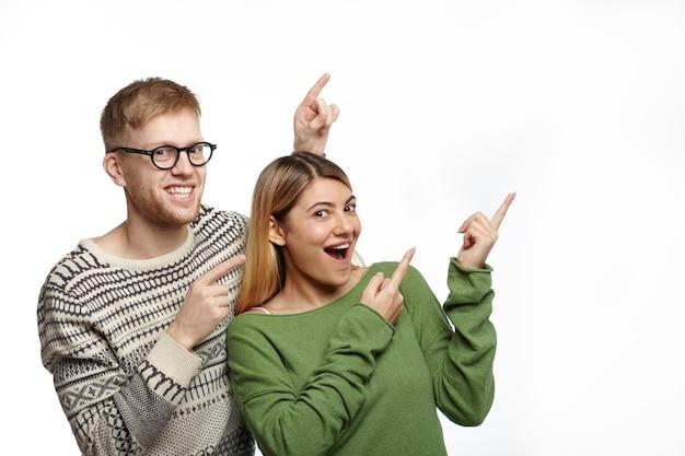 これを見てください。無精ひげとメガネが興奮して見つめ、空白の白いコピースペースの壁に指を指している感情的な大喜びの若い美しい女性とスタイリッシュな男性の孤立したショット