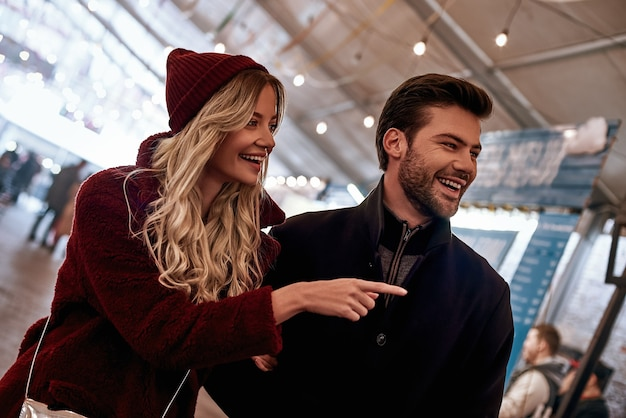 Посмотри на это. счастливая молодая радостная пара гуляет по уличному продовольственному рынку. осенний сезон, белокурая женщина в красной кепке, ее парень смеется, они на уличном рынке.