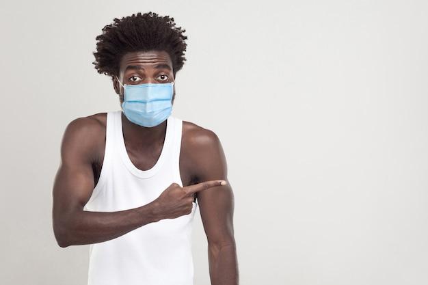 Посмотри на это. портрет смешного молодого человека в белой рубашке с хирургической медицинской маской, стоящей и показывающей или делящей пустое пространство копии на фоне. крытая студия выстрел, изолированные на сером фоне.