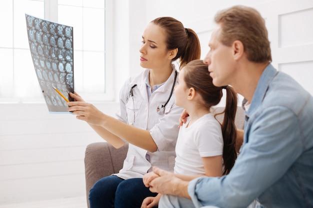 この場所を見てください。フレンドリーな資格のある若い専門家がmri脳スキャンを実演し、患者の家族が彼女の話を注意深く聞きながら病気の原因を指摘します