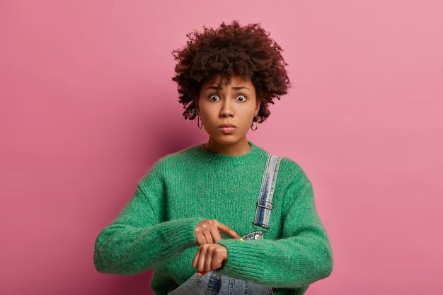 時間を見てください。心配している暗い肌の巻き毛の女性モデルが手首を指さし、締め切りに戸惑い、遅れ、神経質に見え、緑のセーターを着て、恥ずかしい表情をして、屋内でポーズをとる