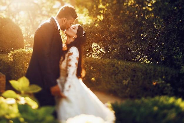 夕方の庭でキスしている美しい結婚式のカップルで上から見てください