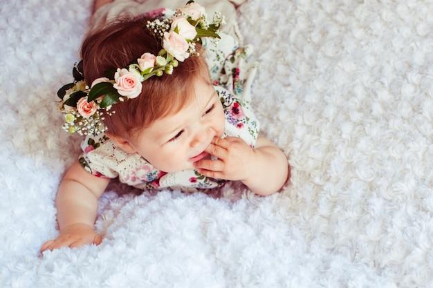 Посмотрите сверху на очаровательную маленькую девочку, лежащую на пушистом одеяле в корзине