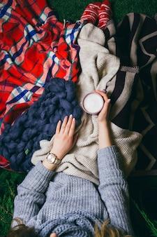 Взгляд сверху на женщину, лежащую под цветными пледами с чашкой латте