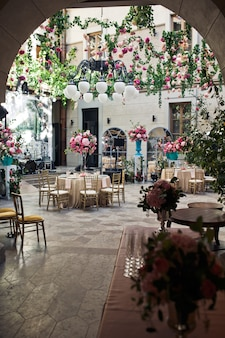 Look from afar at backyard decorated with flowers for wedding dinner