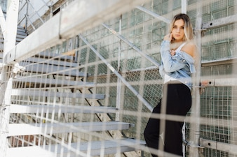 Look from behind a cage at stunning blonde standing in industrial building