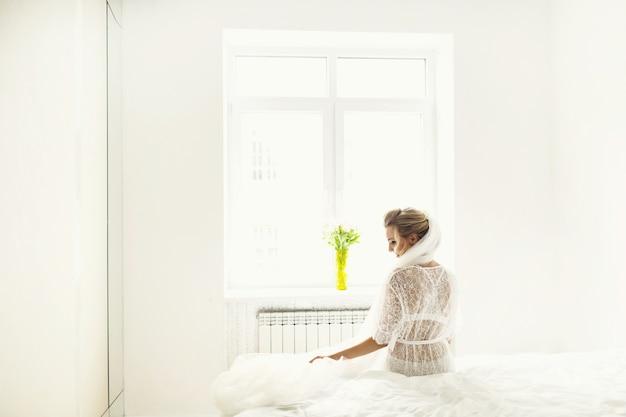 Взгляд сзади у невесты в длинной белой завесе, сидящей в нижнем белье на кровати