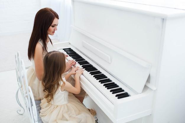 Взгляд из-за у матери и дочери, играющей на белом пианино