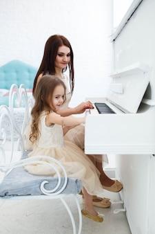 白いピアノを演奏する母と娘の背後から見てください