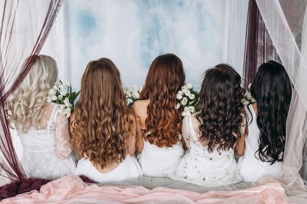 Взгляд сзади у женщин, сидящих на кровати с белыми тюльпанами