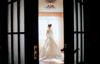 Look from behind the door at a pretty bride standing in a luxury hotel room