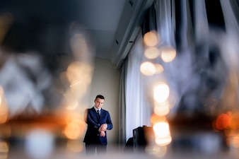 Look from behind the glasses with whisky at handsome groom standing before a window