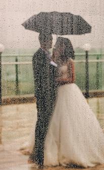 Umbの下に立っている結婚式の夫婦の窓の後ろから見る