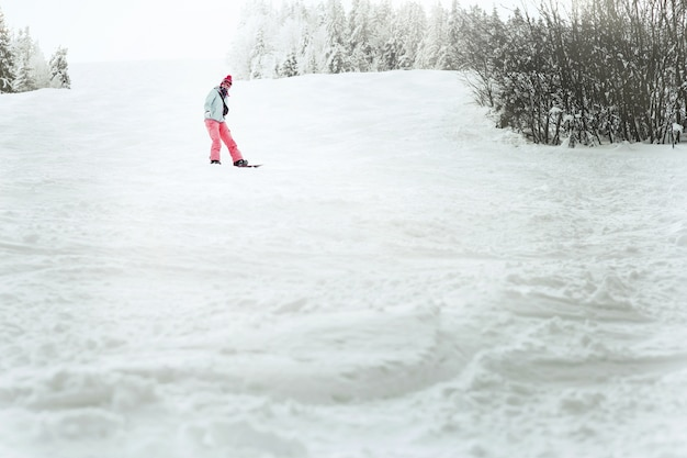 彼女のスノーボードの丘を下っている青いスキージャケットの女性の下から見てください