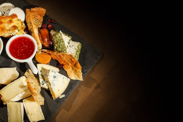 Look from above at black dish with blue cheese, camembert, brie