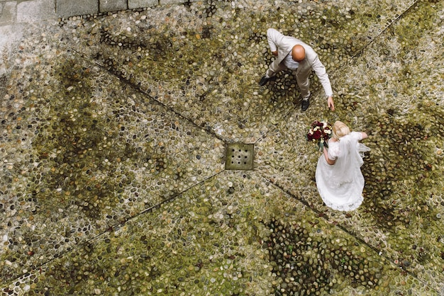 Look from above at bride and groom walking across the backyard