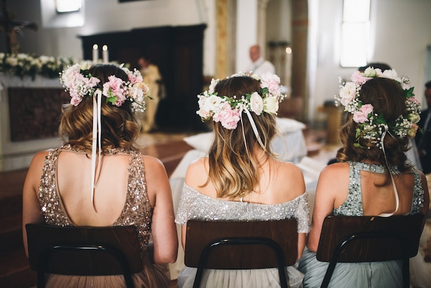 Look from behind at bridesmaids sitting on the chairs in the chu
