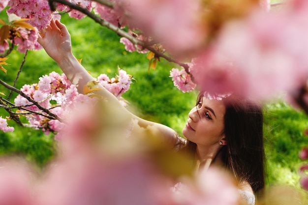 Look from above at charming young woman standing under blooming sakura tree