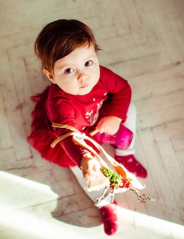 Look from above at child in red dress sitting on the floor