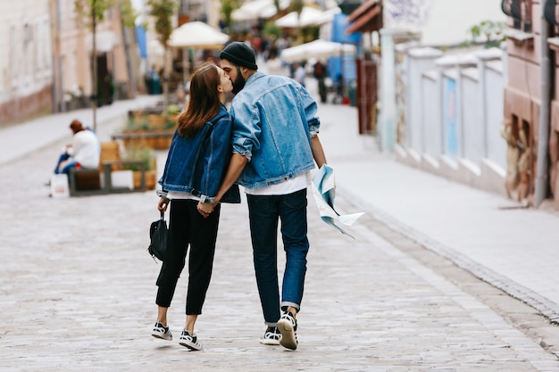 Look from behind at the couple of tourists holding their hands together while walking around the city