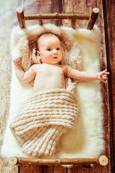 Look from above at little baby lying on wooden bed with white fu