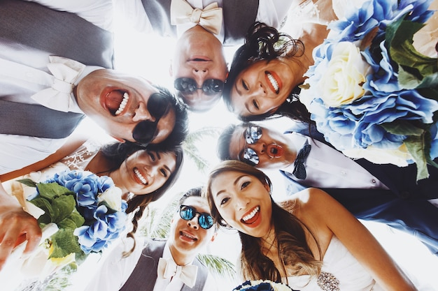 Look from below at newlyweds and friends hugging outside