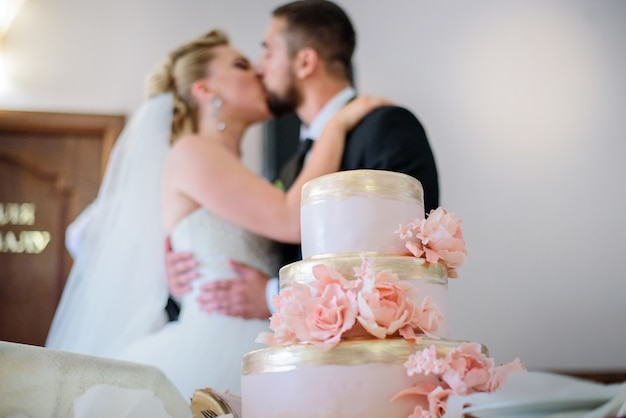 Look from behind pink wedding cake at couple kissing each other tender
