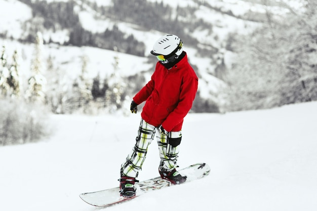 Look from behind the snowboarder in red jacket at mountain hills covered with snow