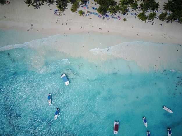 Look from above at turquoise water along golden beach somewhere in dominican republic
