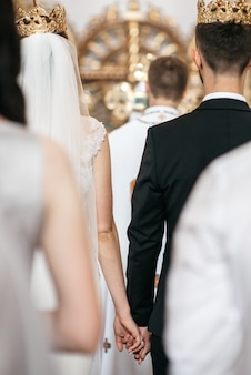 Look from behind at wedding couple standing in the crowns during the ceremony