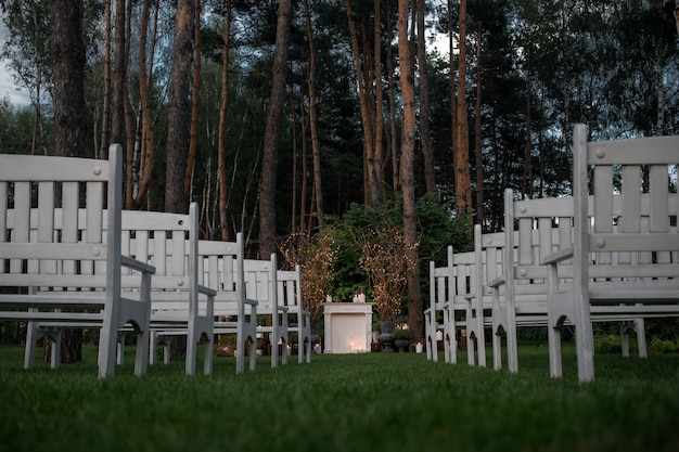 Look from  below at white benches standing before place for wedd