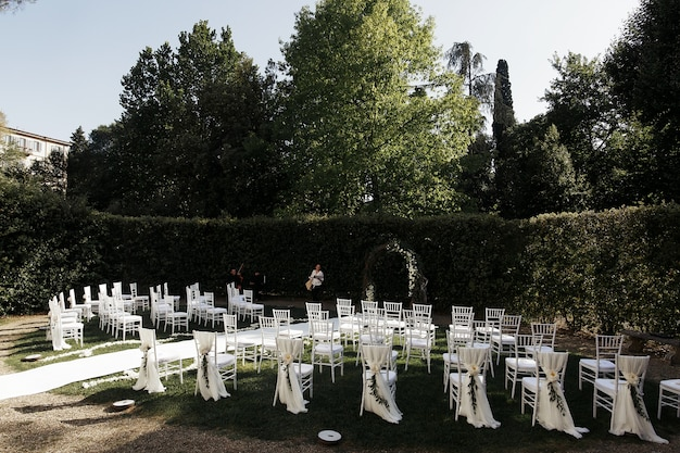 Look from behind at white chairs arranged for wedding ceremony