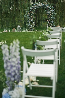 Look from behind at white chairs standing on the green lawn before wedding altar