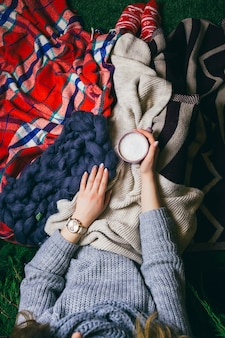 Look from above at woman lying under colorful plaids with cup of latte
