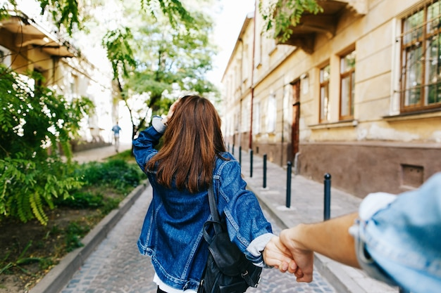 Look from behind at young woman holding man's hand in 'follow me' pose
