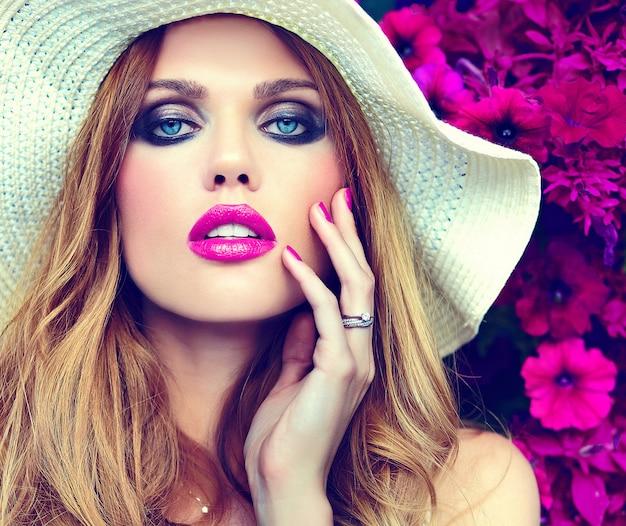 Высокая мода look.glamor крупным планом портрет модели красивая сексуальная стильная блондинка молодая женщина с ярким макияжем и розовыми губами с идеально чистой кожей в шляпе возле летних цветов