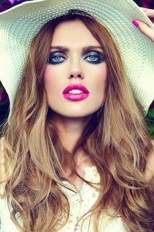 帽子と青い目で完璧なきれいな肌と明るいメイクとピンクの唇と美しいセクシーなスタイリッシュな金髪の若い女性モデルのファッション性の高いlook.glamorのクローズアップの肖像画