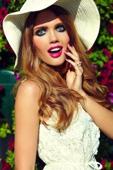 ファッション性の高いlook.glamorは、夏の花の近くの帽子で完璧なきれいな肌と明るい化粧とピンクの唇で美しいセクシーなスタイリッシュな金髪の若い女性モデルを驚かせた