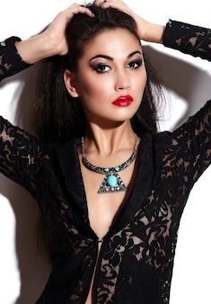 Высокая мода look.glamor крупным планом портрет красивой сексуальной стильной брюнетки кавказской модели молодой женщины с ярким макияжем, с красными губами, с идеально чистой кожей с украшениями из черной ткани