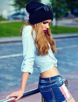 ファッション性の高いlook.glamorライフスタイルブロンド女性女の子モデルカジュアルなジーンズのショートパンツ布メガネで黒い帽子の通りで屋外